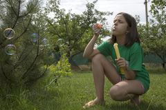 Girl blows soap bubbles on a summer sunny day. A girl blows soap bubbles on a summer sunny day Stock Image