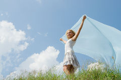 A girl with blue. A girl with a blue cloth against the sky Royalty Free Stock Image