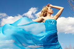 Girl in blue. A young girl in streaming blue dress Royalty Free Stock Image