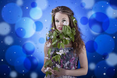 Girl on blue abstract background with flowers in hand. Studio shot Stock Images