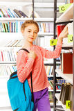 Girl with blue bag stands near shelf in library Royalty Free Stock Image