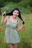 Girl with blue band plays with her hair in poppy field stock image