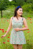 Girl with blue band stands in poppy field. Beautiful girl plays in poppy field in a nice day Royalty Free Stock Image