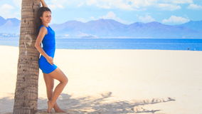 Girl in blue barefoot leans on palm trunk under palm shadow. European long-legged girl in short blue frock barefoot leans on palm trunk under palm shadow against stock footage