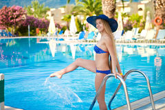 Girl in a blue bathing suit down to the pool royalty free stock photography