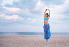 Girl in blue belly dance costume in the air Royalty Free Stock Photo