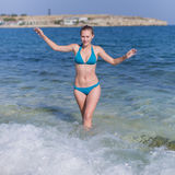 Girl in blue bikini comes from seawater. Girl with arms raised goes in sea. Attractive young woman in blue bikini comes from seawater with arms raised, square Stock Photos