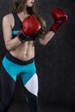 Girl in blue and black making a punch, side view Royalty Free Stock Photo