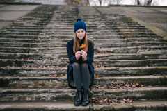 The girl in a blue cap sits on steps Royalty Free Stock Photography