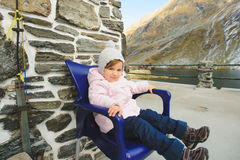 Girl on Blue Chair. Girl sitting on blue chair on porch Royalty Free Stock Image
