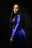 Girl in blue clothes on a black background. Stylish hairstyle, dreadlocks. Black woman. Girl with an unusual hairdo. Black long hair. dreadlocks Royalty Free Stock Photo
