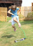 Girl in blue clothes jumping thru sprinkler Royalty Free Stock Photos
