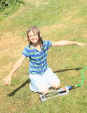 Girl in blue clothes playing with sprinkler Royalty Free Stock Photo