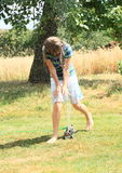 Girl in blue clothes running thru sprinkler Royalty Free Stock Photo