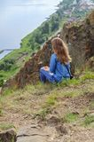 A girl in blue clothes is sitting on the edge of a cliff stock image