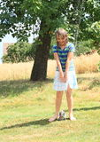 Girl in blue clothes standing above sprinkler Royalty Free Stock Photography