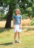 Girl in blue clothes standing above sprinkler Royalty Free Stock Photos