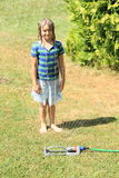 Girl in blue clothes standing behind sprinkler Royalty Free Stock Photography