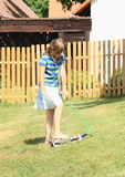 Girl in blue clothes stepping on sprinkler Royalty Free Stock Photos