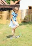 Girl in blue clothes walking thru sprinkler Stock Photo