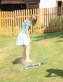 Girl in blue clothes washing foot on sprinkler Royalty Free Stock Images