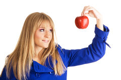 Girl in blue coat holding an apple Royalty Free Stock Image