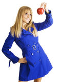 Girl in blue coat holding an apple Stock Photo