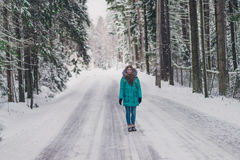 Girl in the blue coat on the road in cold winter forest. Cheerful winter mood in women. A girl walking in winter park. Happy winter time Royalty Free Stock Photography