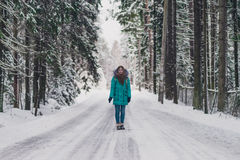 Girl in the blue coat on the road in cold winter forest. Cheerful winter mood in women. A girl walking in winter park. Happy winter time Royalty Free Stock Photo
