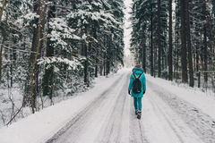 Girl in the blue coat on the road in cold winter forest. Cheerful winter mood in women. A girl walking in winter park. Happy winter time Stock Image