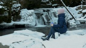 Girl in blue coat sitting with a mug on a background of icy waterfall and rocks in a snow-covered coniferous forest. Winter