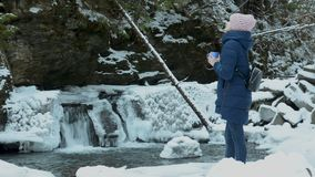 Girl in blue coat standing with a mug on a background of icy waterfall and rocks in a snow-covered coniferous forest. Winter