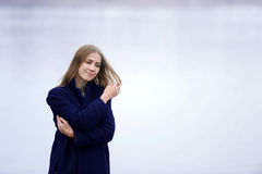 The girl in a blue coat walks along the river Stock Photography