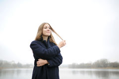The girl in a blue coat walks along the river Stock Images