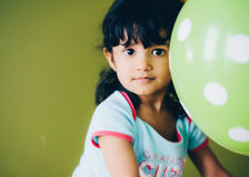 Girl in Blue Crew Neck Shirt Holding a Green Polka Dot Print Balloon Royalty Free Stock Photo