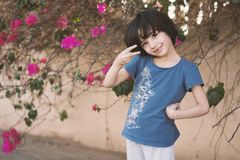 Girl In Blue Crew-neck T-shirt Next To Pink Petaled Flower Stock Photos