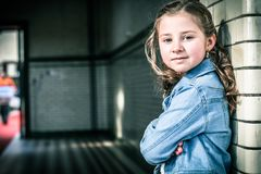 Girl in Blue Denim Jacket Leaning on Gray Wall royalty free stock photography