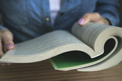Girl in the blue denim shirt reading a paperback book Stock Photos