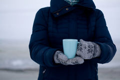 Girl in blue down jacket and gloves holding a cup of tea Stock Photos