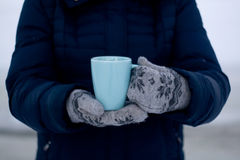 Girl in blue down jacket and gloves holding a cup of tea Royalty Free Stock Images