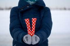 Girl in blue down jacket and gloves holding a letter of fabric Stock Photography