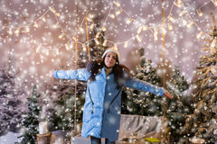 Girl in blue down jacket rejoicing because of snowing standing n. Ear a swing with a blanket under the flashlights in a snow-covered park with spruce trees stock photography