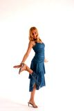 Girl in Blue Dress. Teenage girl with long blond hair wearing dark blue prom dress and high heel shoes against white background Royalty Free Stock Photo