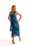 Girl in Blue Dress. Teenage girl with long blond hair wearing dark blue prom dress and high heel shoes against white background Stock Photo