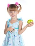 A girl in a blue dress with an apple Royalty Free Stock Image
