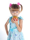 A girl in a blue dress with an apple Stock Image