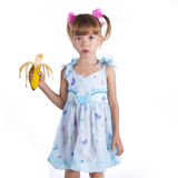 A girl in a blue dress with a banana Stock Image