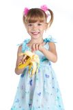 A girl in a blue dress with a banana Royalty Free Stock Photography