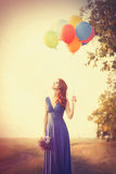Girl in blue dress with bouquet and balloons Royalty Free Stock Images