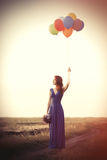 Girl in blue dress with bouquet and balloons Stock Image
